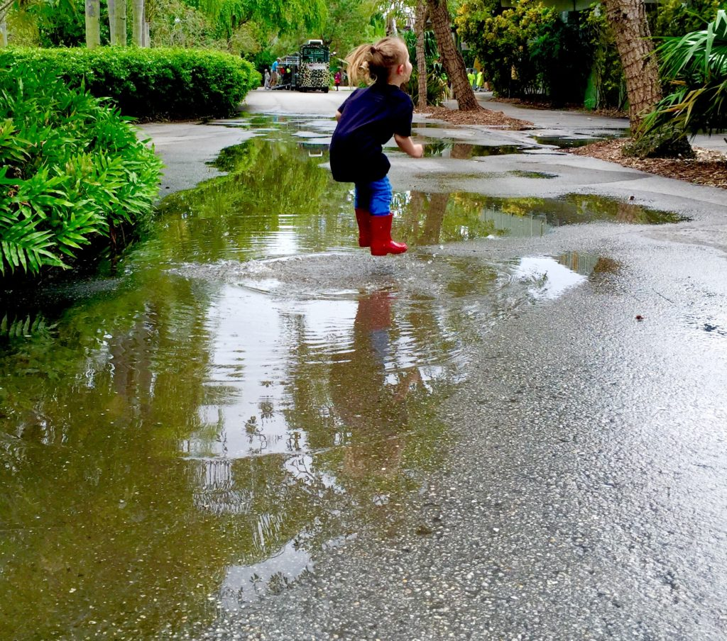 girl jumping in a puddle rainbows wellies
