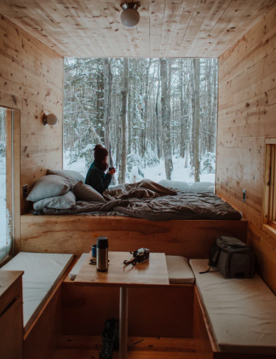 woman sitting by the window in t a tiny house in the woods in winter